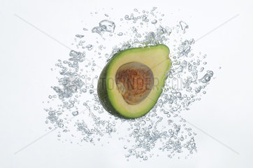Avocado half submerged in sparkling water