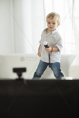 Little boy standing on sofa holding toy microphone