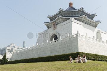 Children sitting on grass by Chiang Kai-shek Memorial Hall  Taipei  Taiwan