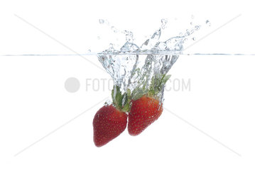 Strawberries splashing into water