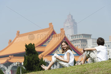 Girl sitting on grass with brother near National Concert Hall  Chiang Kai-Shek Memorial Hall  Taipei  Taiwan