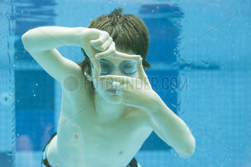 Boy swimming underwater in swimming pool  hands forming finger frame