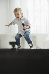 Little boy jumping on sofa with microphone in hand