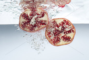 Pomegranate halves submerged in water