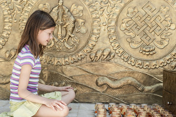 Girl sitting on floor in front of prayer candles
