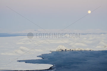 Moon rising over coast of Iceland