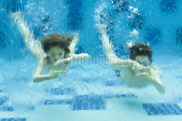 Brother and sister swimming underwater in swimming pool  hands forming finger frames