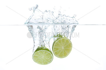 Lime halves splashing into water