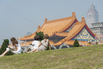 Children sitting on grass overlooking National Concert Hall  Chiang Kai-Shek Memorial Hall  Taipei  Taiwan