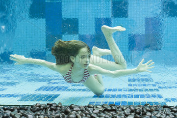 Girl swimming underwater in swimming pool