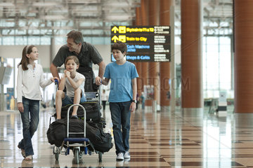 Family pushing luggage cart in airport