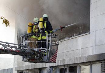 Berlin  Deutschland  Feuerwehrmaenner auf einer Drehleiter bei Loescharbeiten