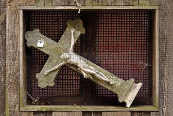 uraltes Kreuz in einer Fensternische  Symbol Krise der Kirche