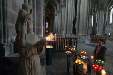 Reims  Frankreich  Kerzen vor einer Skulptur eines Heiligen in der Kathedrale Notre-Dame