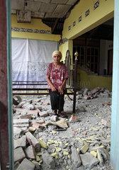 Kampung Bedang  Indonesien  eine Frau sitzt auf einem Bettgestell in ihrem zerstoerten Haus