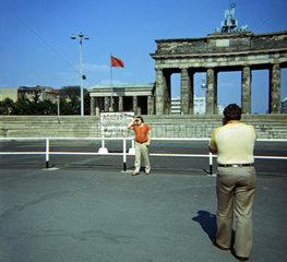 Berlin  Deutschland  Mann fotografiert seinen Freund vor der Berliner Mauer und dem Brandenburger Tor