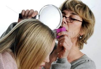 Mutter untersucht Kopf der Tochter auf Laeuse