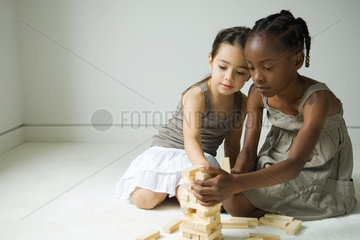 Two girls crouching  building tower with blocks together