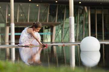 Girl placing flower on surface of water