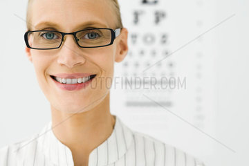 Young woman wearing glasses  eye chart in background  portrait