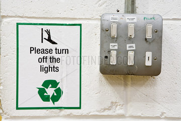 Sign reminding to turn off lights posted beside light switches