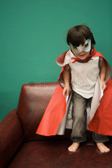 Boy in costume standing on sofa