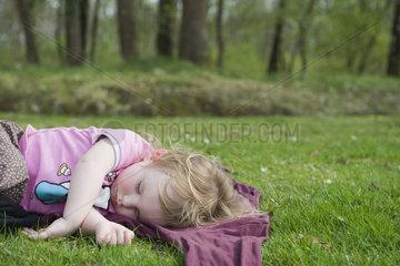 Toddler girl taking a nap outdoors
