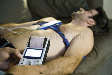 Doctor performing portable EKG (electrocardiogram) on patient in home