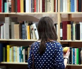 Frau steht vor einem Buchregal