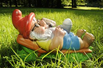 Gartenzwerg liegt im Gras  Symbol Urlaub