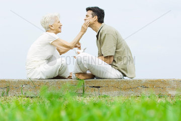 Senior woman and adult son sitting face to face outdoors  sharing take-out food
