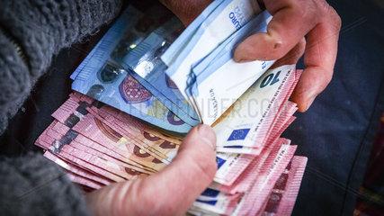 Mann zaehlt Euro Geldscheine