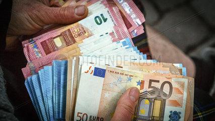 Mann haelt Euro Geldscheine in den Haenden
