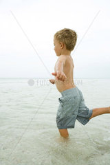 Little boy standing in shallow water  posed to kick