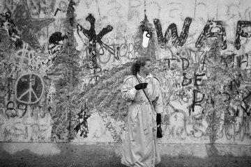 Berlin  Deutschland  eine Frau wartet an der Mauer