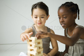 Two girls building tower with blocks together