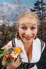 Hamburg  Deutschland  Frau im Dirndl mit einem Blumenstrauss