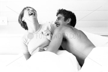Couple in bed  both laughing