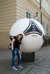 Lemberg  Ukraine  junge Frau posiert vor einem uebergrossen Modell des adidas Tango 12