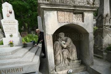 Lemberg  Ukraine  Frau an einem ukrainisch-orthodoxen Grab auf dem Lytschakiwski-Friedhof