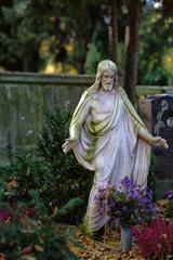 Berlin  Deutschland  Jesusfigur auf einem von Herbstlaub bedecktem Grab auf dem Alten Luisenfriedhof