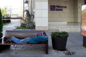 Bukarest  Rumaenien  ein Mann schaeft auf einer Parkbank