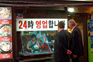 Seoul  Suedkorea Zwei europaeische Geschaeftsleute vor einem Imbiss