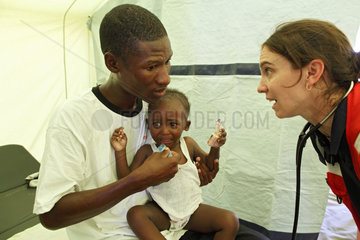 Carrefour  Haiti  Dr. Marie Roy  re.  behandelt eien Vater mit seinem Kind im Field Hospital