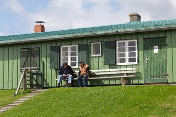 Tuemlauer Koog  Deutschland  zwei Maenner sitzen auf einer Bank und unterhalten sich