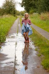 Ruehstaedt  Deutschland  ein Maedchen spielt in einer Pfuetze auf einem Landweg