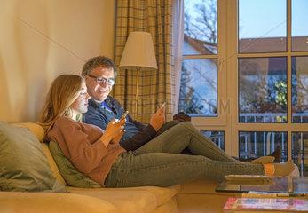 Vater und Tochter spielen zuhause gemeinsam mit dem Smartphone