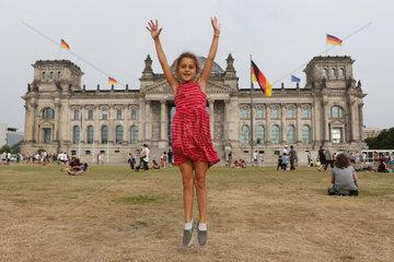 Berlin  Deutschland  kleines Maedchen huepft vor dem Reichstagsgebaeude froehlich in die Luft