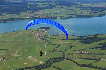 Schwangau  Deutschland  ein Gleitschirmflieger fliegt uebers Allgaeu