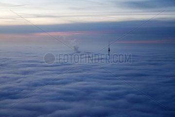 Berlin  Deutschland  der Berliner Fernsehturm ragt bei Daemmerung aus den Wolken heraus